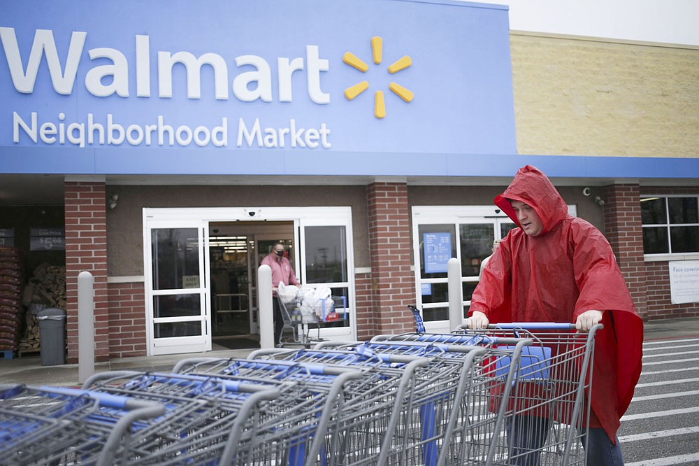 Walmart employee Jacob Morrison pushes carts, Friday, March 12, 2021 at a Walmart Neighborhood Market in Bentonville. Check out nwaonline.com/210313Daily/ for today's photo gallery.  (NWA Democrat-Gazette/Charlie Kaijo)