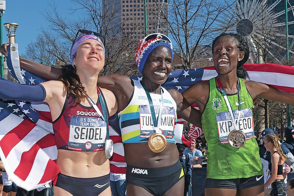 FILE - First-place finisher Aliphine Tuliamuk, center, second-place finisher Molly Seidel, left, and third-place finisher Sally Kipyego, right, celebrate on the podium after running the women's U.S. Olympic marathon trials in Atlanta, in this Saturday, Feb. 29, 2020, file photo. When the Tokyo Summer Games were postponed, U.S. Olympic marathon trials champion Aliphine Tuliamuk decided with her fiance last year to have a baby instead of waiting. (AP Photo/John Amis, File)