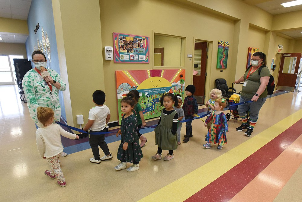 Teachers, including Katie Jennings (left), lead students through a hallway to a play area on Wednesday March 17 2021 at the Benton County Sunshine School and Development Center. (NWA Demorcrat-Gazette/Flip Putthoff)