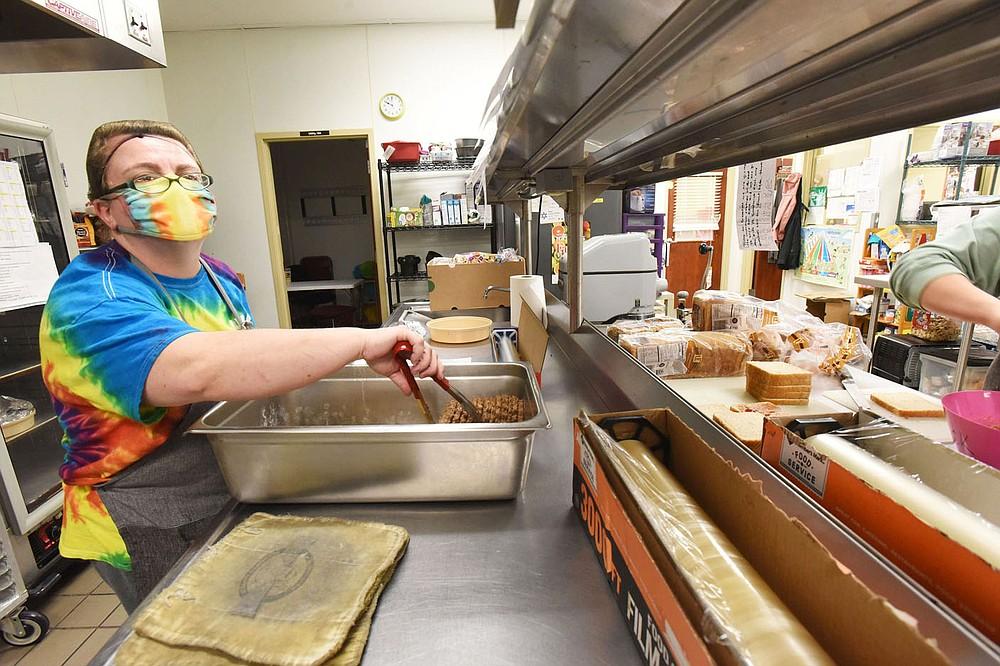 Becky Holt cooks lunch in the kitchen on Wednesday March 17 2021 at the Benton County Sunshine School and Development Center. (NWA Demorcrat-Gazette/Flip Putthoff)