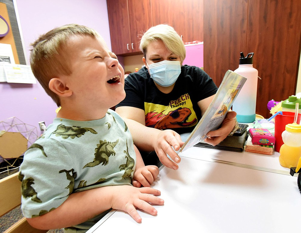 Tabitha Mayberry, speech therapist, and her student laugh together on Wednesday March 17 2021 while reading a story at the Benton County Sunshine School and Development Center in Rogers. (NWA Democrat-Gazette/Flip Putthoff)