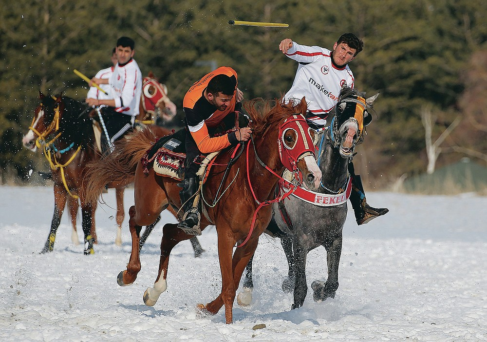 """A rider throws the javelin during a game of Cirit, a traditional Turkish equestrian sport that dates back to the martial horsemen who spearheaded the historical conquests of central Asia's Turkic tribes, between the Comrades and the Experts local sporting clubs, in Erzurum, eastern Turkey, Friday, March 5, 2021. The game that was developed more than a 1,000 years ago, revolves around a rider trying to spear his or her opponent with a """"javelin"""" - these days, a rubber-tipped, 100 centimeter (40 inch) length of wood. A rider from each opposing team, which can number up to a dozen players, face each other, alternately acting as the thrower and the rider being chased. Cirit was popular within the Ottoman empire, before it was banned as in the early 19th century. However, its popularity returned as is now one of many traditional sports encouraged by the government and tournaments are often arranged during festivals or to celebrate weddings. (AP Photo/Kenan Asyali)"""