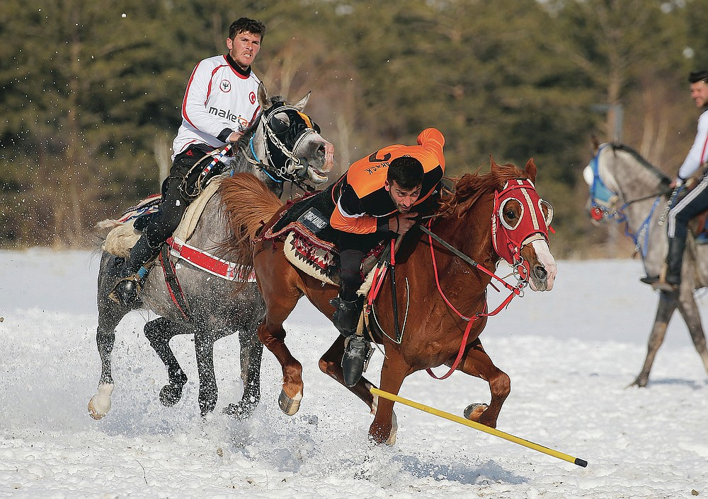"""A rider dodges the javelin thrown by an opponent during a game of Cirit, a traditional Turkish equestrian sport that dates back to the martial horsemen who spearheaded the historical conquests of central Asia's Turkic tribes, between the Comrades and the Experts local sporting clubs, in Erzurum, eastern Turkey, Friday, March 5, 2021. The game that was developed more than a 1,000 years ago, revolves around a rider trying to spear his or her opponent with a """"javelin"""" - these days, a rubber-tipped, 100 centimeter (40 inch) length of wood. A rider from each opposing team, which can number up to a dozen players, face each other, alternately acting as the thrower and the rider being chased. Cirit was popular within the Ottoman empire, before it was banned as in the early 19th century. However, its popularity returned as is now one of many traditional sports encouraged by the government and tournaments are often arranged during festivals or to celebrate weddings. (AP Photo/Kenan Asyali)"""