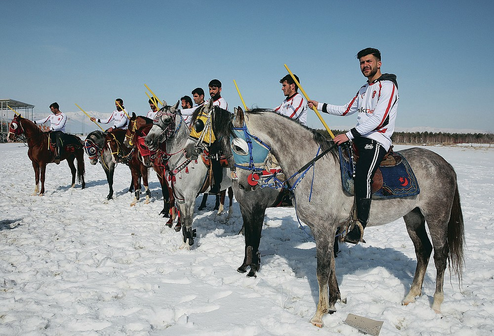 """Riders, members of the Dadas (Comrades) local sporting club, gather for a game of Cirit, a traditional Turkish equestrian sport that dates back to the martial horsemen who spearheaded the historical conquests of central Asia's Turkic tribes, between the Comrades and the Experts local sporting clubs, in Erzurum, eastern Turkey, Friday, March 5, 2021. The game that was developed more than a 1,000 years ago, revolves around a rider trying to spear his or her opponent with a """"javelin"""" - these days, a rubber-tipped, 100 centimeter (40 inch) length of wood. A rider from each opposing team, which can number up to a dozen players, face each other, alternately acting as the thrower and the rider being chased. Cirit was popular within the Ottoman empire, before it was banned as in the early 19th century. However, its popularity returned as is now one of many traditional sports encouraged by the government and tournaments are often arranged during festivals or to celebrate weddings. (AP Photo/Kenan Asyali)"""