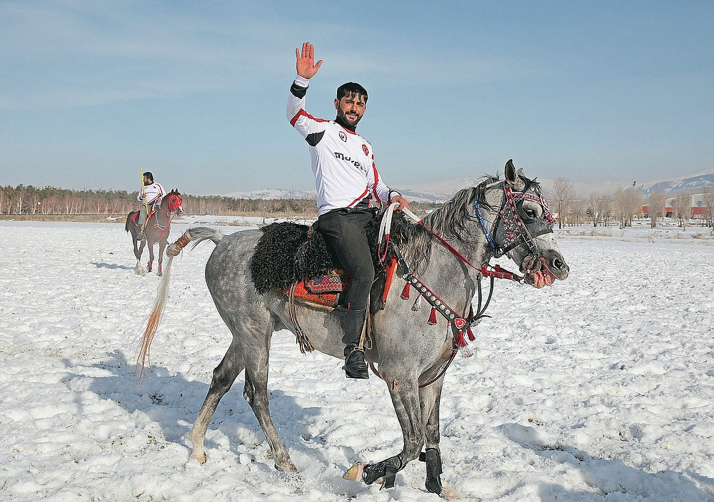 """A rider, member of the Dadas (Comrades) local sporting club, waves to the crowd following a game of Cirit, a traditional Turkish equestrian sport that dates back to the martial horsemen who spearheaded the historical conquests of central Asia's Turkic tribes, between the Comrades and the Experts local sporting clubs, in Erzurum, eastern Turkey, Friday, March 5, 2021. The game that was developed more than a 1,000 years ago, revolves around a rider trying to spear his or her opponent with a """"javelin"""" - these days, a rubber-tipped, 100 centimeter (40 inch) length of wood. A rider from each opposing team, which can number up to a dozen players, face each other, alternately acting as the thrower and the rider being chased. Cirit was popular within the Ottoman empire, before it was banned as in the early 19th century. However, its popularity returned as is now one of many traditional sports encouraged by the government and tournaments are often arranged during festivals or to celebrate weddings. (AP Photo/Kenan Asyali)"""