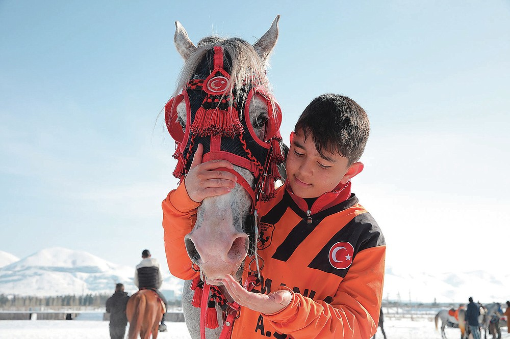 """Thirteen-year-old Muhammed Rasit, the youngest member of Uzmanlar, (Experts) sports club, cuddles his horse prior to a game of Cirit, a traditional Turkish equestrian sport that dates back to the martial horsemen who spearheaded the historical conquests of central Asia's Turkic tribes, between the Comrades and the Experts local sporting clubs, in Erzurum, eastern Turkey, Friday, March 5, 2021. The game that was developed more than a 1,000 years ago, revolves around a rider trying to spear his or her opponent with a """"javelin"""" - these days, a rubber-tipped, 100 centimeter (40 inch) length of wood. A rider from each opposing team, which can number up to a dozen players, face each other, alternately acting as the thrower and the rider being chased. Cirit was popular within the Ottoman empire, before it was banned as in the early 19th century. However, its popularity returned as is now one of many traditional sports encouraged by the government and tournaments are often arranged during festivals or to celebrate weddings. (AP Photo/Kenan Asyali)"""