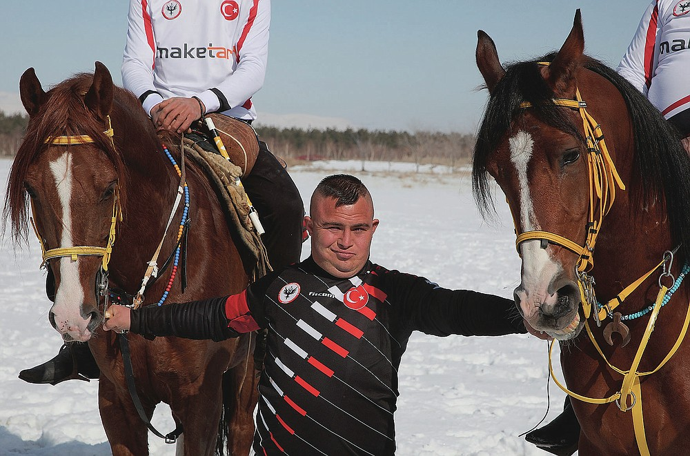 """Selcuk Davulcu, 31, a horse groom for the Dadas (Comrades) local sporting club, prepares the horses during a game of Cirit, a traditional Turkish equestrian sport that dates back to the martial horsemen who spearheaded the historical conquests of central Asia's Turkic tribes, between the Comrades and the Experts local sporting clubs, in Erzurum, eastern Turkey, Friday, March 5, 2021. The club officials said that Davulcu, a man with Down syndrome has been communicating with people just for the last four years thanks to the horses as they played a big role on his rehabilitation.The game that was developed more than a 1,000 years ago, revolves around a rider trying to spear his or her opponent with a """"javelin"""" - these days, a rubber-tipped, 100 centimeter (40 inch) length of wood. A rider from each opposing team, which can number up to a dozen players, face each other, alternately acting as the thrower and the rider being chased. Cirit was popular within the Ottoman empire, before it was banned as in the early 19th century. (AP Photo/Kenan Asyali)"""