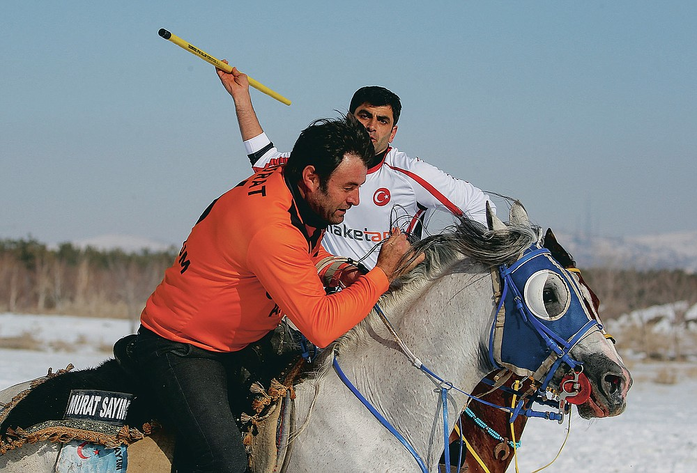 """A rider is about to throw the javelin during a game of Cirit, a traditional Turkish equestrian sport that dates back to the martial horsemen who spearheaded the historical conquests of central Asia's Turkic tribes, between the Comrades and the Experts local sporting clubs, in Erzurum, eastern Turkey, Friday, March 5, 2021. The game that was developed more than a 1,000 years ago, revolves around a rider trying to spear his or her opponent with a """"javelin"""" - these days, a rubber-tipped, 100 centimeter (40 inch) length of wood. A rider from each opposing team, which can number up to a dozen players, face each other, alternately acting as the thrower and the rider being chased. Cirit was popular within the Ottoman empire, before it was banned as in the early 19th century. However, its popularity returned as is now one of many traditional sports encouraged by the government and tournaments are often arranged during festivals or to celebrate weddings. (AP Photo/Kenan Asyali)"""