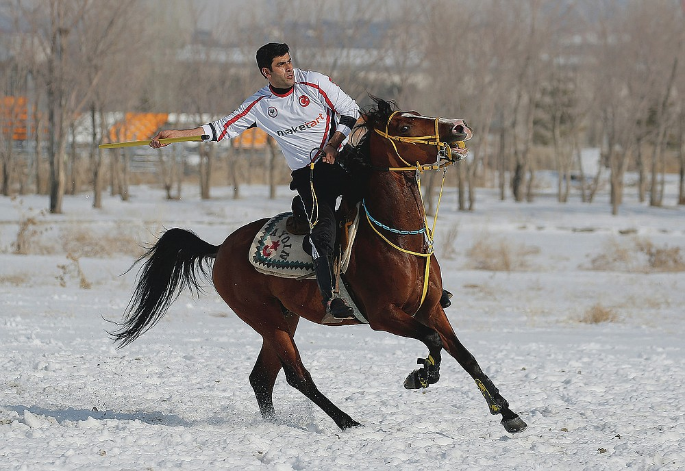 """A rider prepares to throw the javelin during a game of Cirit, a traditional Turkish equestrian sport that dates back to the martial horsemen who spearheaded the historical conquests of central Asia's Turkic tribes, between the Comrades and the Experts local sporting clubs, in Erzurum, eastern Turkey, Friday, March 5, 2021. The game that was developed more than a 1,000 years ago, revolves around a rider trying to spear his or her opponent with a """"javelin"""" - these days, a rubber-tipped, 100 centimeter (40 inch) length of wood. A rider from each opposing team, which can number up to a dozen players, face each other, alternately acting as the thrower and the rider being chased. Cirit was popular within the Ottoman empire, before it was banned as in the early 19th century. However, its popularity returned as is now one of many traditional sports encouraged by the government and tournaments are often arranged during festivals or to celebrate weddings. (AP Photo/Kenan Asyali)"""