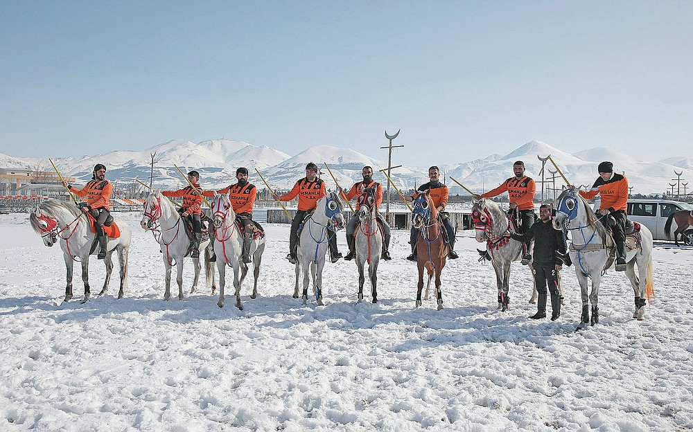 """Riders, members of the Uzmanlar, (Experts) sports club, pose for photographs prior to a game of Cirit, a traditional Turkish equestrian sport that dates back to the martial horsemen who spearheaded the historical conquests of central Asia's Turkic tribes, between the Comrades and the Experts local sporting clubs, in Erzurum, eastern Turkey, Friday, March 5, 2021. The game that was developed more than a 1,000 years ago, revolves around a rider trying to spear his or her opponent with a """"javelin"""" - these days, a rubber-tipped, 100 centimeter (40 inch) length of wood. A rider from each opposing team, which can number up to a dozen players, face each other, alternately acting as the thrower and the rider being chased. Cirit was popular within the Ottoman empire, before it was banned as in the early 19th century. However, its popularity returned as is now one of many traditional sports encouraged by the government and tournaments are often arranged during festivals or to celebrate weddings. (AP Photo/Kenan Asyali)"""