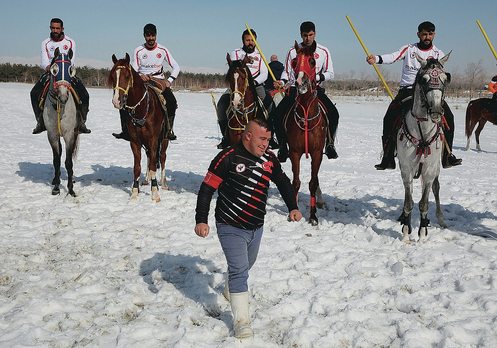 """Selcuk Davulcu, 31, a horse groom for the Dadas (Comrades) local sporting club, leaves the ground prior to a game of Cirit, a traditional Turkish equestrian sport that dates back to the martial horsemen who spearheaded the historical conquests of central Asia's Turkic tribes, between the Comrades and the Experts local sporting clubs, in Erzurum, eastern Turkey, Friday, March 5, 2021. The club officials said that Davulcu, a man with Down syndrome has been communicating with people just for the last four years thanks to the horses as they played a big role on his rehabilitation.The game that was developed more than a 1,000 years ago, revolves around a rider trying to spear his or her opponent with a """"javelin"""" - these days, a rubber-tipped, 100 centimeter (40 inch) length of wood. A rider from each opposing team, which can number up to a dozen players, face each other, alternately acting as the thrower and the rider being chased. Cirit was popular within the Ottoman empire, before it was banned as in the early 19th century. (AP Photo/Kenan Asyali)"""
