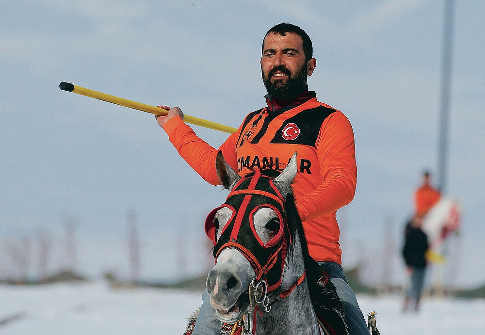 """A rider is about to throw the the javelin during a game of Cirit, a traditional Turkish equestrian sport that dates back to the martial horsemen who spearheaded the historical conquests of central Asia's Turkic tribes, between the Comrades and the Experts local sporting clubs, in Erzurum, eastern Turkey, Friday, March 5, 2021. The game that was developed more than a 1,000 years ago, revolves around a rider trying to spear his or her opponent with a """"javelin"""" - these days, a rubber-tipped, 100 centimeter (40 inch) length of wood. A rider from each opposing team, which can number up to a dozen players, face each other, alternately acting as the thrower and the rider being chased. Cirit was popular within the Ottoman empire, before it was banned as in the early 19th century. However, its popularity returned as is now one of many traditional sports encouraged by the government and tournaments are often arranged during festivals or to celebrate weddings. (AP Photo/Kenan Asyali)"""