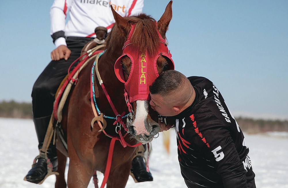 """Selcuk Davulcu, 31, a horse groom for the Dadas (Comrades) local sporting club, cuddles a horse prior to a game of Cirit, a traditional Turkish equestrian sport that dates back to the martial horsemen who spearheaded the historical conquests of central Asia's Turkic tribes, between the Comrades and the Experts local sporting clubs, in Erzurum, eastern Turkey, Friday, March 5, 2021. The club officials said that Davulcu, a man with Down syndrome has been communicating with people just for the last four years thanks to the horses as they played a big role on his rehabilitation.The game that was developed more than a 1,000 years ago, revolves around a rider trying to spear his or her opponent with a """"javelin"""" - these days, a rubber-tipped, 100 centimeter (40 inch) length of wood. A rider from each opposing team, which can number up to a dozen players, face each other, alternately acting as the thrower and the rider being chased. Cirit was popular within the Ottoman empire, before it was banned as in the early 19th century. (AP Photo/Kenan Asyali)"""
