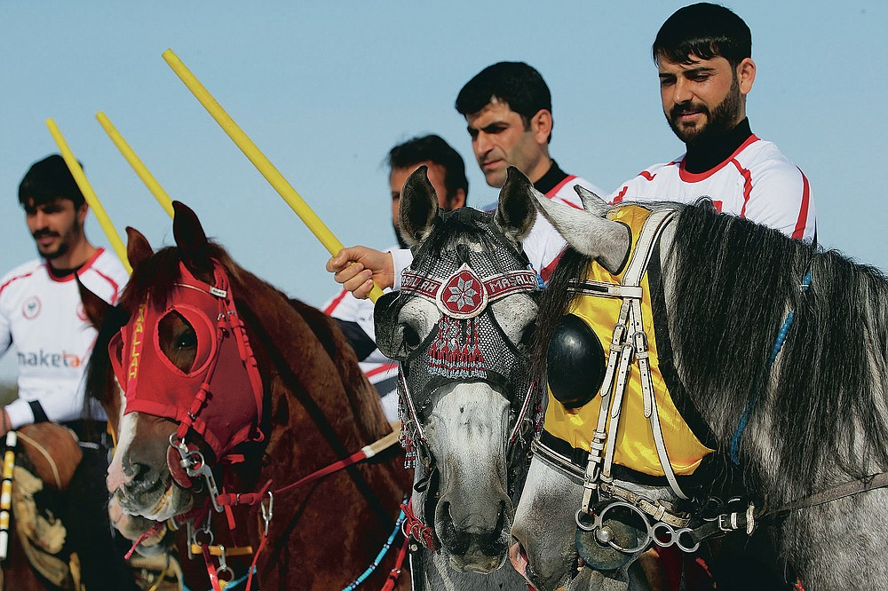 """Riders, members of the Dadas (Comrades) local sporting club, pose for photographs prior to a game of Cirit, a traditional Turkish equestrian sport that dates back to the martial horsemen who spearheaded the historical conquests of central Asia's Turkic tribes, between the Comrades and the Experts local sporting clubs, in Erzurum, eastern Turkey, Friday, March 5, 2021. The game that was developed more than a 1,000 years ago, revolves around a rider trying to spear his or her opponent with a """"javelin"""" - these days, a rubber-tipped, 100 centimeter (40 inch) length of wood. A rider from each opposing team, which can number up to a dozen players, face each other, alternately acting as the thrower and the rider being chased. Cirit was popular within the Ottoman empire, before it was banned as in the early 19th century. However, its popularity returned as is now one of many traditional sports encouraged by the government and tournaments are often arranged during festivals or to celebrate weddings. (AP Photo/Kenan Asyali)"""