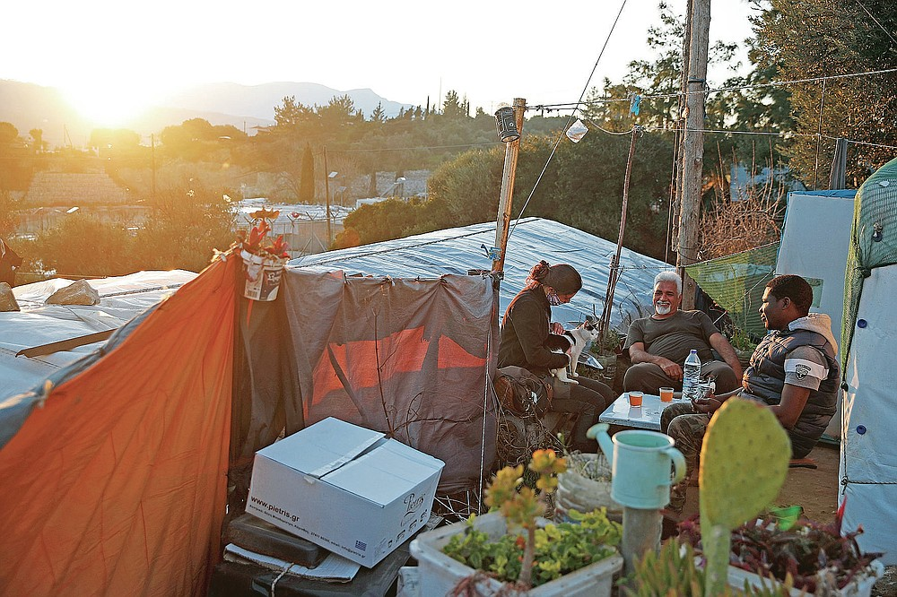 Migrants sit outside of a makeshift tent as the suns sets outside the perimeter of the overcrowded refugee camp at the port of Vathy on the eastern Aegean island of Samos, Greece, Tuesday, Feb. 23, 2021. On a hill above a small island village, the sparkling blue of the Aegean just visible through the pine trees, lies a boy's grave. His first ever boat ride was to be his last - the sea claimed him before his sixth birthday. His 25-year-old father, like so many before him, had hoped for a better life in Europe, far from the violence of his native Afghanistan. But his dreams were dashed on the rocks of Samos, a picturesque Greek island almost touching the Turkish coast. Still devastated from losing his only child, the father has now found himself charged with a felony count of child endangerment. (AP Photo/Thanassis Stavrakis)