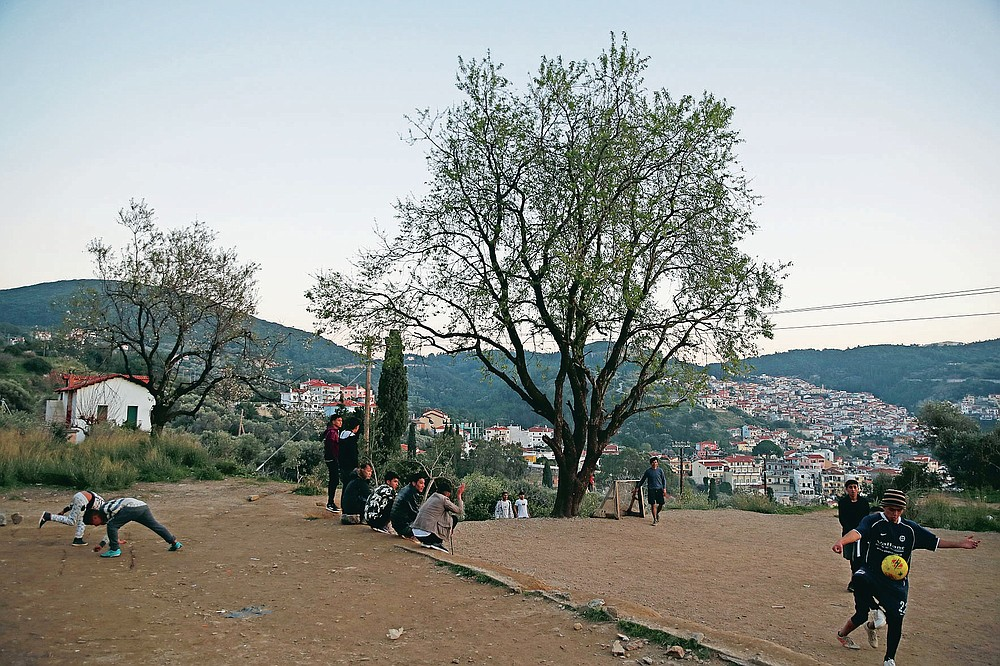 Migrants play soccer outside the perimeter of the overcrowded refugee camp at the port of Vathy on the eastern Aegean island of Samos, Greece, Tuesday, Feb. 23, 2021. On a hill above a small island village, the sparkling blue of the Aegean just visible through the pine trees, lies a boy's grave. His first ever boat ride was to be his last - the sea claimed him before his sixth birthday. His 25-year-old father, like so many before him, had hoped for a better life in Europe, far from the violence of his native Afghanistan. But his dreams were dashed on the rocks of Samos, a picturesque Greek island almost touching the Turkish coast. Still devastated from losing his only child, the father has now found himself charged with a felony count of child endangerment. (AP Photo/Thanassis Stavrakis)
