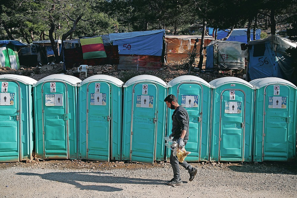 A migrant walks in front of chemical toilets outside the perimeter of the overcrowded refugee camp at the port of Vathy on the eastern Aegean island of Samos, Greece, Wednesday, Feb. 24, 2021. On a hill above a small island village, the sparkling blue of the Aegean just visible through the pine trees, lies a boy's grave. His first ever boat ride was to be his last - the sea claimed him before his sixth birthday. His 25-year-old father, like so many before him, had hoped for a better life in Europe, far from the violence of his native Afghanistan. But his dreams were dashed on the rocks of Samos, a picturesque Greek island almost touching the Turkish coast. Still devastated from losing his only child, the father has now found himself charged with a felony count of child endangerment. (AP Photo/Thanassis Stavrakis)