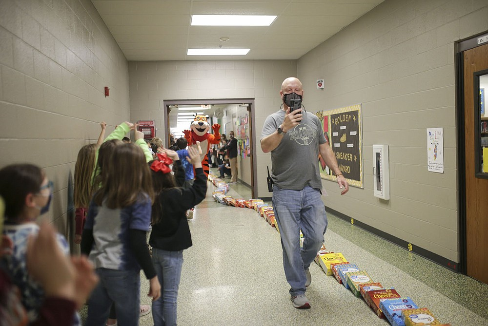 Principal Dan Cox records a live stream as cereal boxes topple, Friday at Bellview Elementary School in Rogers. Several Rogers schools are helping the Samaritan Center by collecting boxes of cereal to feed the hungry. Bellview filled their halls with the cereal boxes to create a domino effect. Check out nwaonline.com/210320Daily/ for today's photo gallery.  (NWA Democrat-Gazette/Charlie Kaijo)