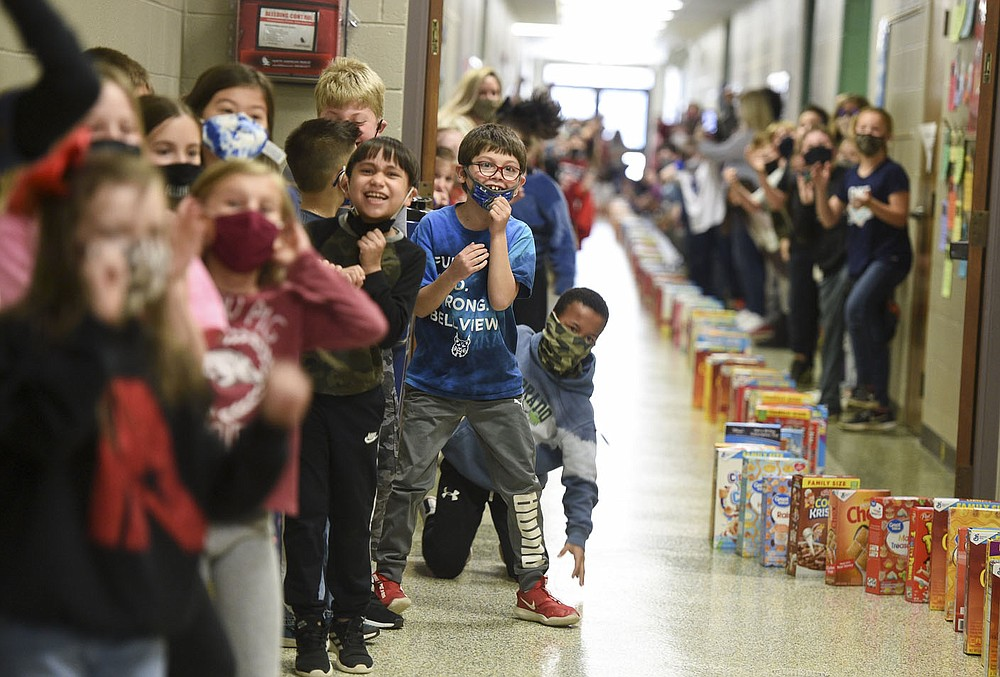 Students cheer as cereal boxes topple, Friday at Bellview Elementary School in Rogers. Several Rogers schools are helping the Samaritan Center by collecting boxes of cereal to feed the hungry. Bellview filled their halls with cereal boxes to create a domino effect. Check out nwaonline.com/210320Daily/ for today's photo gallery.  (NWA Democrat-Gazette/Charlie Kaijo)