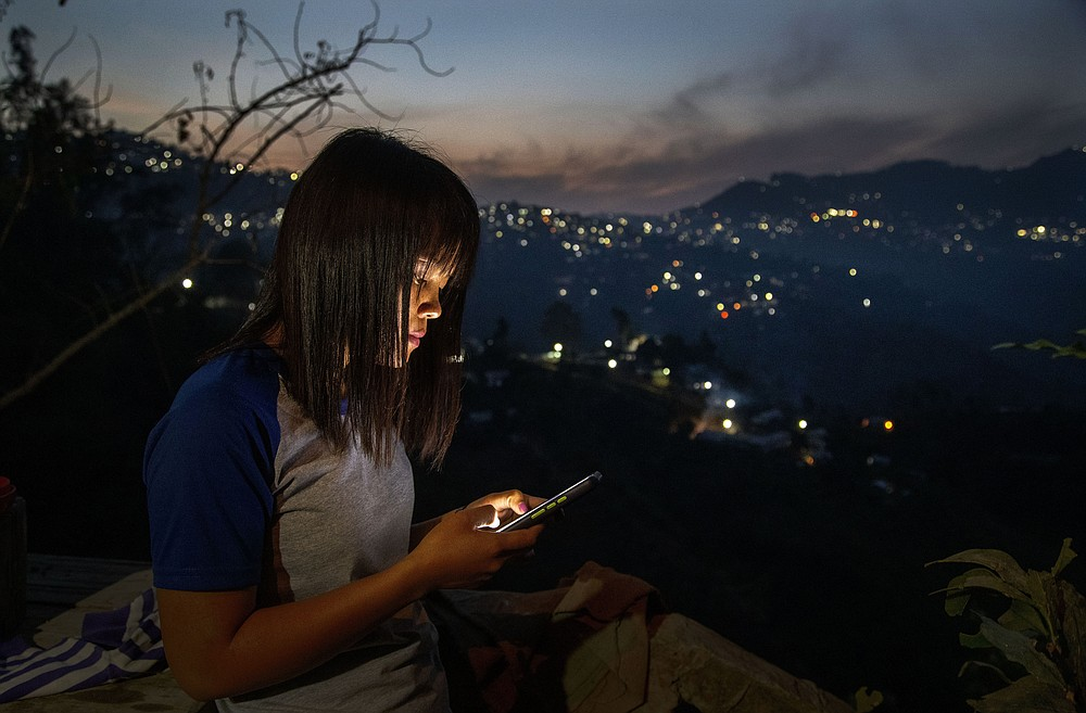 A police officer who fled Myanmar following a military coup looks at her phone at an undisclosed location bordering Myanmar, in the northeastern Indian state of Mizoram, Thursday, March 18, 2021. Villagers in Mizoram have given shelter to 34 Myanmar police personnel and 1 fire fighter, who crossed over to the state over the last two weeks. Those who escaped spend their time watching local television and doing daily chores. Some of them have carried mobile phones and are trying to connect to families they were forced to leave behind. At night, all of them go to sleep on mattresses laid on the floor of a single room. (AP Photo/Anupam Nath)