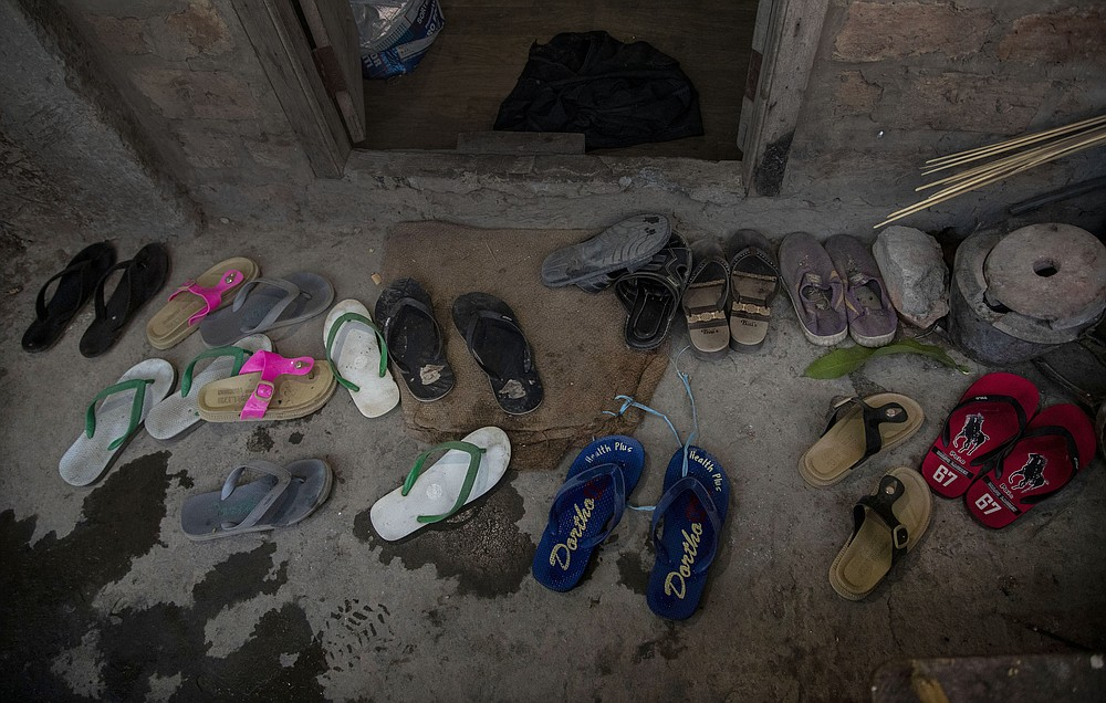 Footwear of police officers, who fled Myanmar following a military coup, lie outside an undisclosed location bordering Myanmar, in the northeastern Indian state of Mizoram, Thursday, March 18, 2021. Villagers in Mizoram have given shelter to 34 Myanmar police personnel and 1 fire fighter, who crossed over to the state over the last two weeks. Those who escaped spend their time watching local television and doing daily chores. Some of them have carried mobile phones and are trying to connect to families they were forced to leave behind. At night, all of them go to sleep on mattresses laid on the floor of a single room. (AP Photo/Anupam Nath)