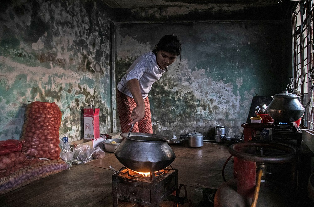 A police officer who fled Myanmar following a military coup cooks a meal at an undisclosed location bordering Myanmar, in the northeastern Indian state of Mizoram, Thursday, March 18, 2021. Villagers in Mizoram have given shelter to 34 Myanmar police personnel and 1 fire fighter, who crossed over to the state over the last two weeks. Those who escaped spend their time watching local television and doing daily chores. Some of them have carried mobile phones and are trying to connect to families they were forced to leave behind. At night, all of them go to sleep on mattresses laid on the floor of a single room. (AP Photo/Anupam Nath)