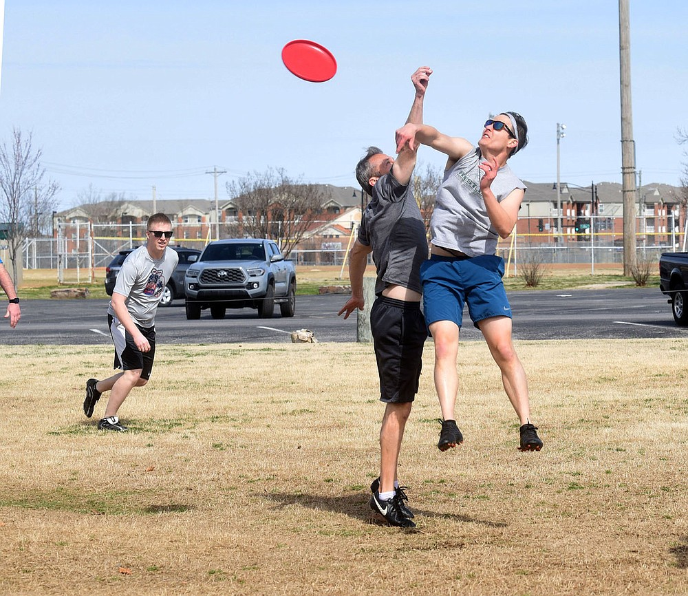 Aaron Smith (right) and teammates play Ultimate Frisbee on Tuesday March 16 2021 at Phillips Park in Bentonville. Included in the April 13 bond proposal is $32.75 million for parks. (NWA Democat-Gazette/Flip Putthoff)
