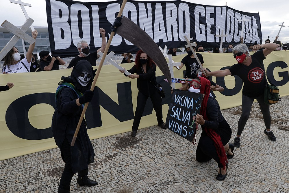 "A demonstrator holds the Portuguese message ""Vaccination saves lives"", below, during a performance with a protester dressed as death and wearing a mock presidential sash, during a protest against President Jair Bolsonaro's handling of the COVID-19 pandemic outside Planalto presidential palace in Brasilia, Brazil, Friday, March 19, 2021. The banner at top reads ""Bolsonaro genocide."" (AP Photo/Eraldo Peres)"
