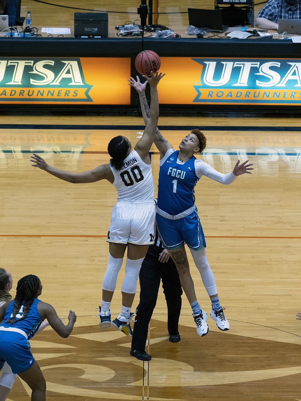 Michigan forward Naz Hilmon (00) jumps the opening tip-off against Florida Gulf Coast guard Kierstan Bell (1) during the first quarter of a college basketball game in the first round of the women's NCAA tournament at the University of Texas San Antonio Convocation Center in San Antonio, Texas, Sunday March 21, 2021. (AP Photo/Michael Thomas)