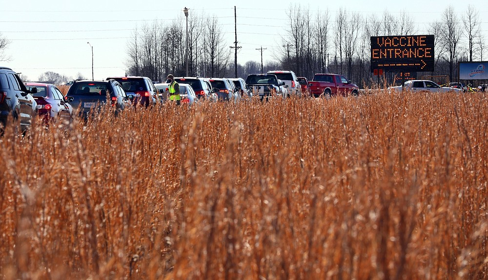 FILE - In this Jan. 22, 2021, file photo, vehicles snake through a line beside a farm field in Poplar Bluff, Mo., for the state's first mass COVID-19 vaccination event. Despite the clamor to speed up the U.S. vaccination drive against COVID-19, the first three months of the rollout suggest faster is not necessarily better. (Robert Cohen/St. Louis Post-Dispatch via AP, File)