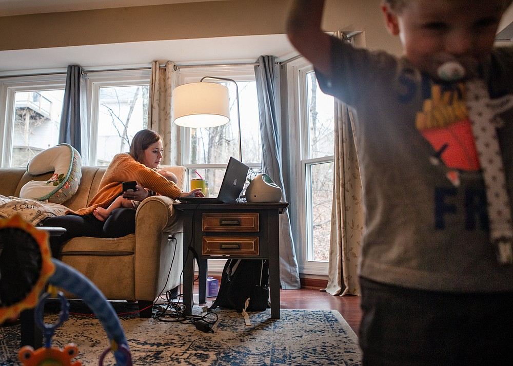 Dr. Elizabeth Bergamini,  pediatrician in suburban St. Louis, searches online for open COVID-19 vaccine appointments while holding her 4-month-old son, Louis, and supervising her 2-year-old son, James Jerome, at her home in Wildwood, Mo., on March 11, 2021. Bergamini drove about 30 people to often out-of-the way vaccination events after the state opened eligibility to those 65 and older Jan. 18 and then expanded further. (Sara Diggins/St. Louis Post-Dispatch via AP)