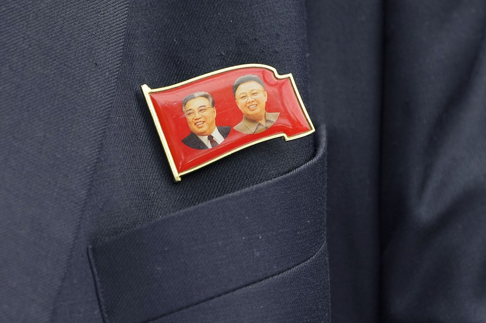 Kim Yu Song, counselor at the North Korean Embassy to Malaysia, wears a pin showing North Korea's former leaders, Kim Il Sung, left, and Kim Jong Il, outside the embassy in Kuala Lumpur, Sunday, March 21, 2021. Malaysia on Friday ordered all North Korean diplomats to leave the country within 48 hours, an escalation of a diplomatic spat over Malaysia's move to extradite a North Korean suspect to the United States on money laundering charges. (AP Photo/Vincent Thian)