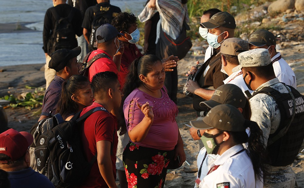 Mexican immigration agents stop people who crossed the Suchiate River, the natural border between Guatemala and Mexico, to see their identification documents as they enforce limits on all but essential travel near Ciudad Hidalgo, Mexico, Monday, March 22, 2021. Agents are forcing those with permission to enter Mexico for work or a visit to use the official border crossing bridge and others are being returned toGuatemala. (AP Photo/Eduardo Verdugo)