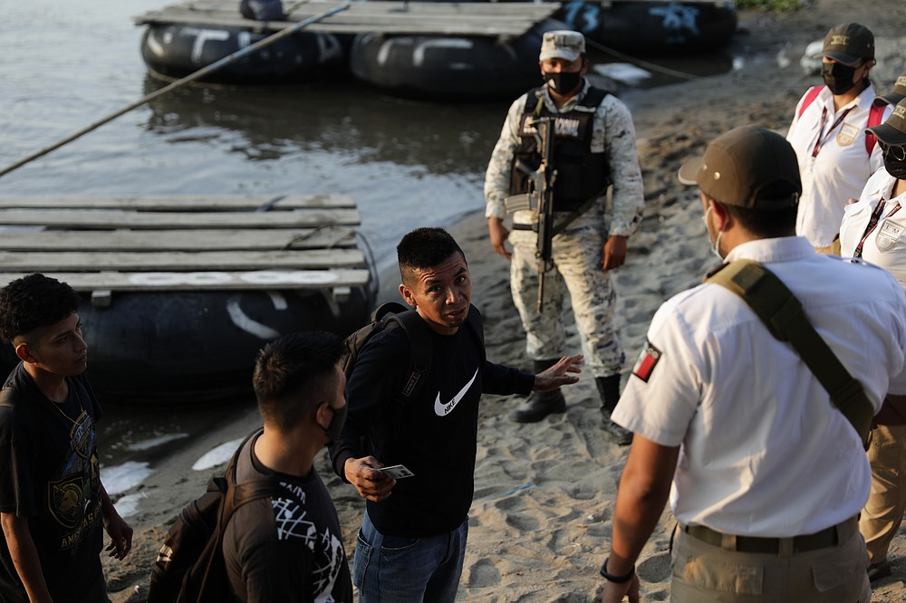 Mexican immigration agents stop people who crossed the Suchiate River, the natural border between Guatemala and Mexico, to see their identification documents as they enforce limits on all but essential travel near Ciudad Hidalgo, Mexico, Monday, March 22, 2021. Agents are forcing those with permission to enter Mexico for work or a visit to use the official border crossing bridge, and those who do not are being returned toGuatemala. (AP Photo/Eduardo Verdugo)