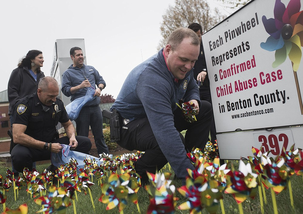 Det. Andrew Corbett (center right) places pinwheels into the ground, Friday, April 3, 2020 at the Bentonville Police Department in Bentonville. Check out nwaonline.com/200404Daily/ for today's photo gallery. (NWA Democrat-Gazette/Charlie Kaijo)  April is child abuse awareness month in Benton County. All law enforcement and child protective agencies that work child abuse cases in Benton County placed pinwheels to signify the confirmed child abuse cases from the previous year. 19 agencies participated, and each agency placed 392 pinwheels at their locations.