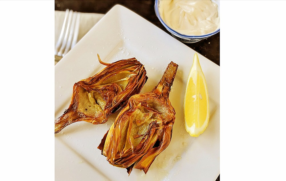 Artichokes halves fried in olive oil can be served with mayonnaise for dipping and wedges of fresh lemon. (TNS/Post-Gazette/Gretchen McKay)