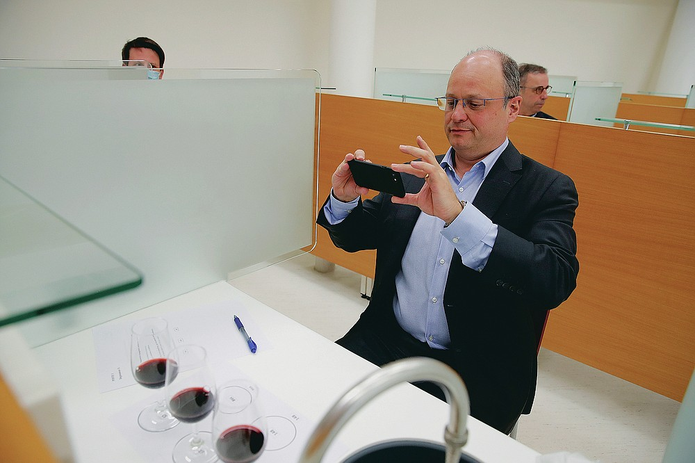 Chief Operating Officer of French National Centre for Space Studies (CNES) Lionel Suchet takes a pictures of glasses of red wine during a tasting of regular bottles and others that spent a year orbiting the world in the International Space Station, at the ISVV in Villenave-d'Ornon, southwestern France, Monday, March 1, 2021. Researchers in Bordeaux are carefully studying a dozen bottles of French wine that returned to Earth after a stay aboard the International Space Station. They're releasing preliminary results Wednesday, March 24, 2021. At a one-of-a-kind tasting this month, 12 connoisseurs sampled one of the space-traveled wines, blindly tasting it alongside a bottle from the same vintage that had stayed in a cellar. (AP Photo/Christophe Ena)