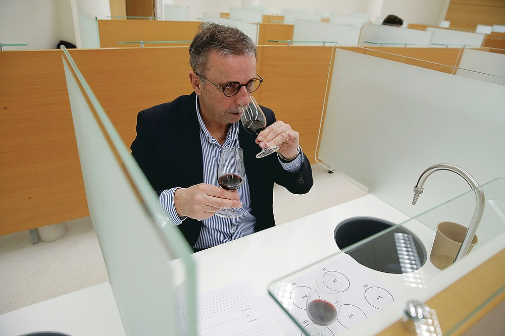 Bordeaux Mayor Pierre Hurmic smells glasses of wine, during a tasting session, with one glass containing wine that spent a year orbiting the world in the International Space Station, at the Institute for Wine and Vine Research in Villenave-d'Ornon, southwestern France, Monday, March 1, 2021. Researchers in Bordeaux are carefully studying a dozen bottles of French wine that returned to Earth after a stay aboard the International Space Station. They're releasing preliminary results Wednesday, March 24, 2021. At a one-of-a-kind tasting this month, 12 connoisseurs sampled one of the space-traveled wines, blindly tasting it alongside a bottle from the same vintage that had stayed in a cellar.  (AP Photo/Christophe Ena)