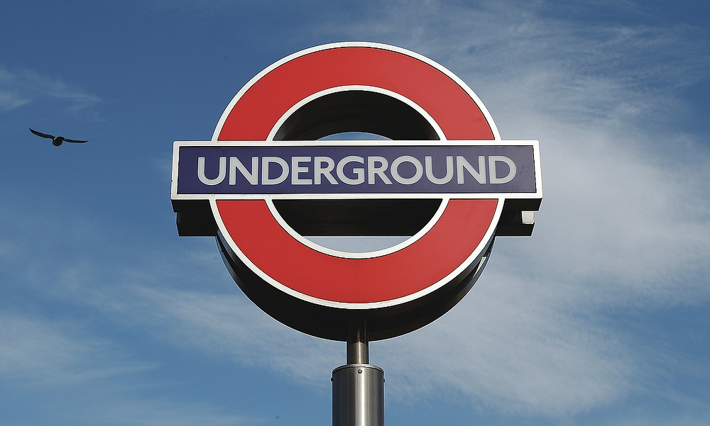 A bird flies above an Underground sign at one of the entrances to King's Cross tube station in London, Friday, March 12, 2021. Even as many of its famous institutions closed during the coronavirus pandemic for most of the past 12 months, London's Underground kept running through three successive lockdowns. Nicknamed the Tube, its staff from cleaners to train drivers take pride in maintaining a system that keeps London's heart beating. (AP Photo/Alastair Grant)