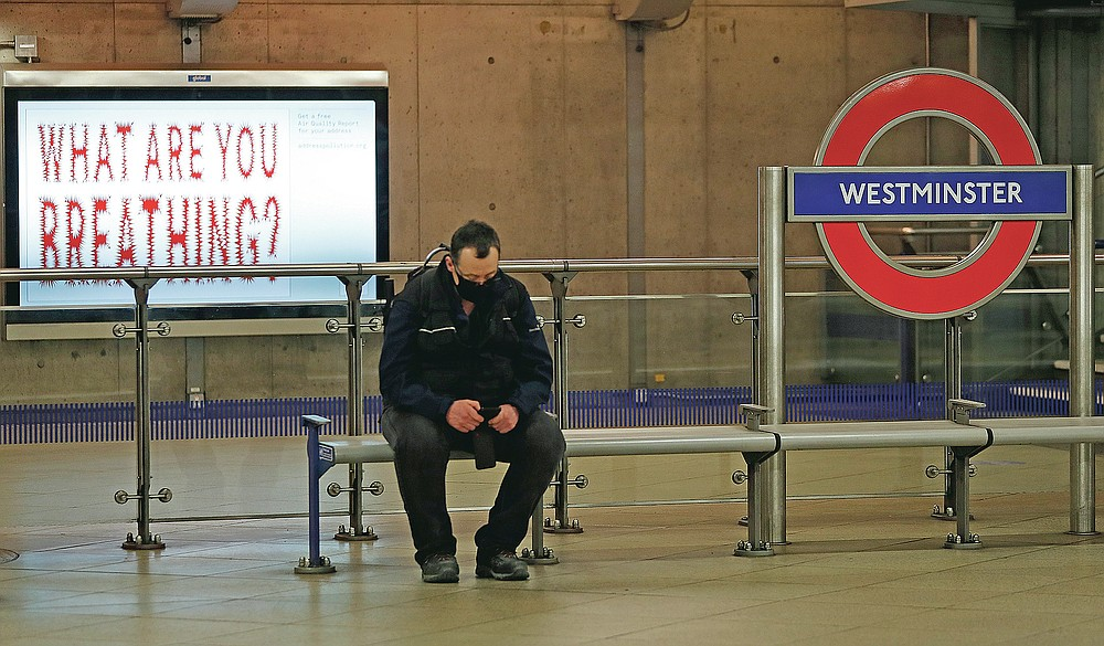 A man sits on a bench waiting for a tube train at Westminster Underground station in London, Wednesday, March 10, 2021. (AP Photo/Alastair Grant)