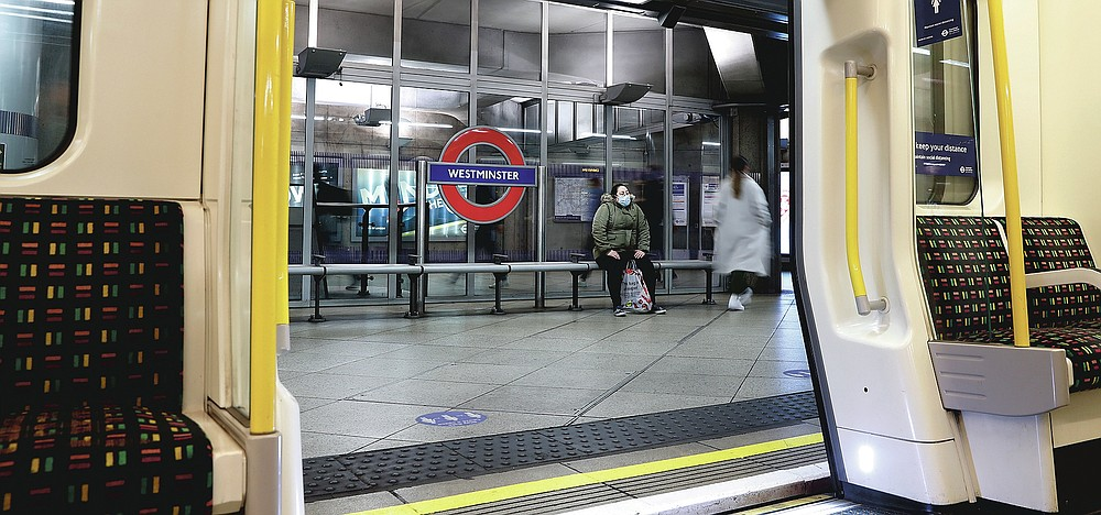 A passenger waits on the platform for a train at Westminster Underground station in London, Friday, March 12, 2021. (AP Photo/Alastair Grant)