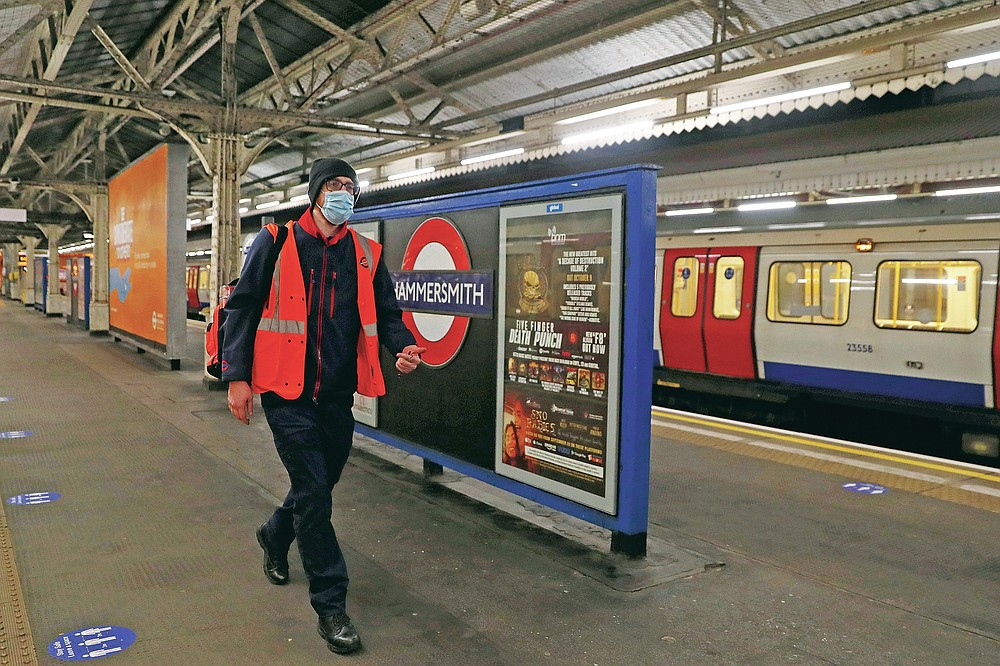 """Joseph Cocks, a tube train driver, walks from the front to the back of the train along the platform at Hammersmith Underground station before taking the train round the Circle Line in London, Wednesday, March 10, 2021. When London came to a stop as a nationwide coronavirus lockdown was imposed a year ago, the Underground kept running as an essential service. But it was a strange and unnerving experience for its workers. Cocks, a driver on the subway's Circle Line that loops around the city center, said he could """"count the number of people who got on the train on one hand.""""(AP Photo/Alastair Grant)"""