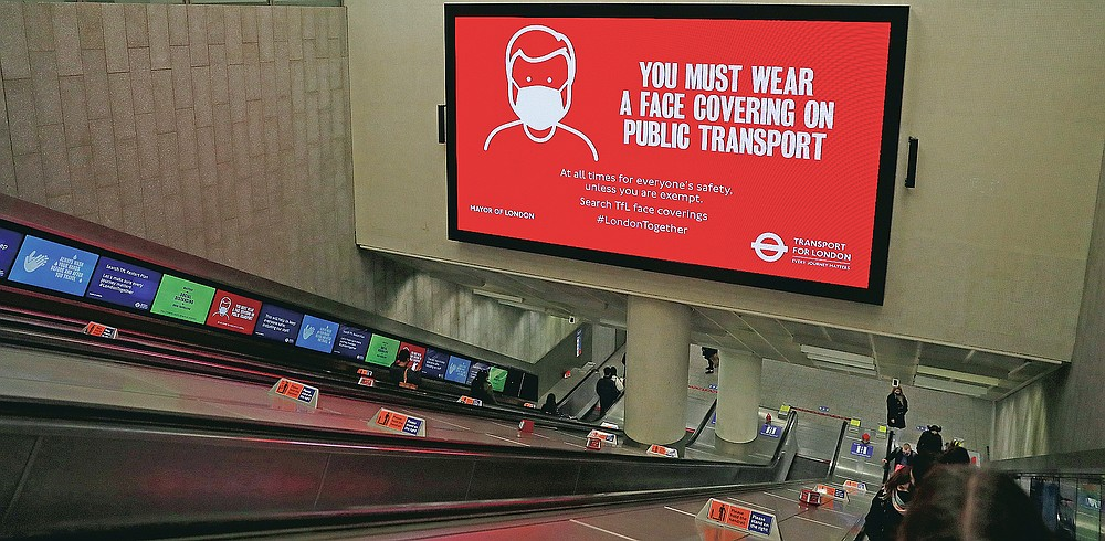 Customers ride the the escalators at King's Cross Underground station, with a coronavirus information advert on a large screen over the escalators in London, Wednesday, March 10, 2021. (AP Photo/Alastair Grant)