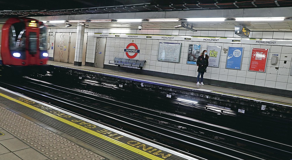 A lone passenger waits and looks at the information screen as a train arrives at Monument Underground station in London, Friday, March 12, 2021. Even as many of its famous institutions closed during the coronavirus pandemic for most of the past 12 months, London's Underground kept running through three successive lockdowns. (AP Photo/Alastair Grant)