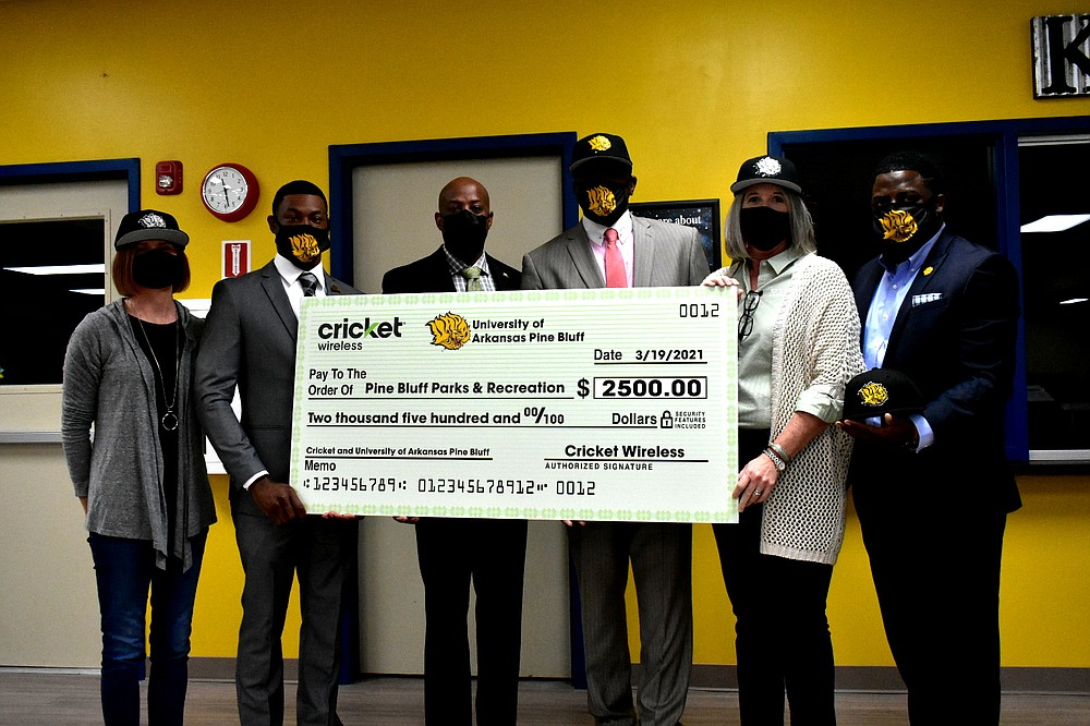 From left, Cricket Wireless marketing manager Hayley Schaberg, UAPB assistant director of student-athlete academic services Juwan Parker, Pine Bluff Parks and Recreation Director Samuel Glover, UAPB interim Athletic Director Chris Robinson, Cricket indirect sales executive Beth Burgess and UAPB director of community outreach Cameo Stokes pose with a display check representing Cricket's donation to the Parks and Recreation Department at the Pine Bluff Community Center on Wednesday, March 24, 2021. (Pine Bluff Commercial/I.C. Murrell)