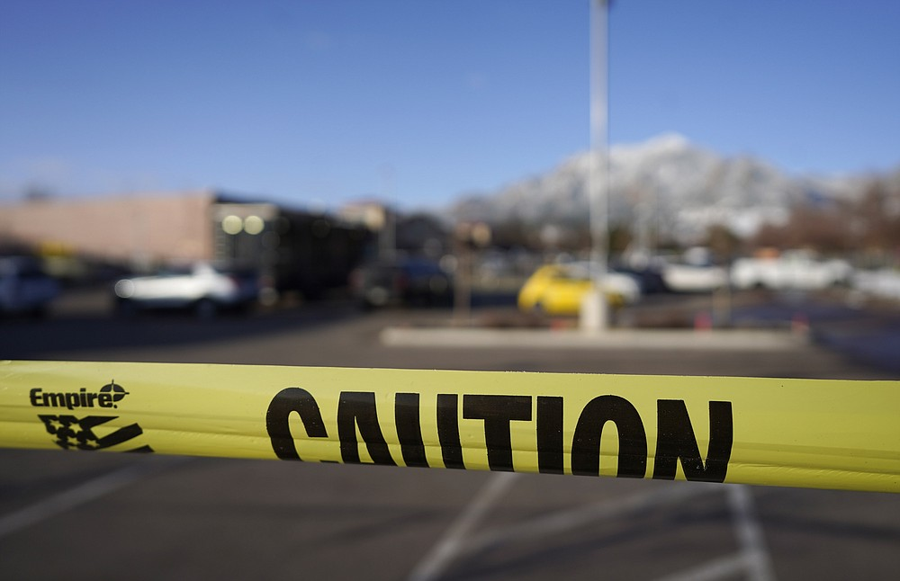 Caution tape marks the parking lot outside a King Soopers grocery store where a mass shooting took place a day earlier in Boulder, Colo., Tuesday, March 23, 2021.  (AP Photo/David Zalubowski)