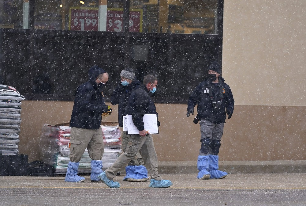 Investigators deal with light snow as they collect evidence in the parking lot where a mass shooting took place in a King Soopers grocery store Tuesday, March 23, 2021, in Boulder, Colo. (AP Photo/David Zalubowski)