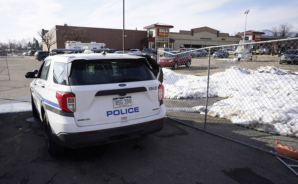 Police drive past a makeshift fence put up around the parking lot outside a King Soopers grocery store where a mass shooting took place Tuesday, March 23, 2021, in Boulder, Colo. (AP Photo/David Zalubowski)