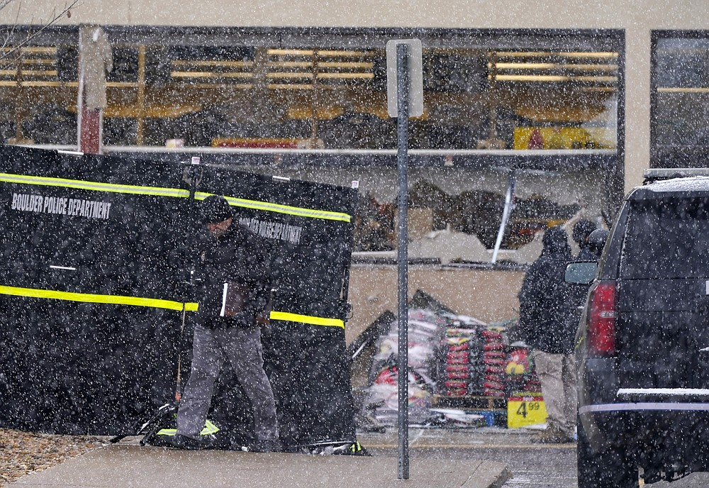 A snow squall envelops investigators as they collect evidence around the parking lot where a mass shooting took place in a King Soopers grocery store Tuesday, March 23, 2021, in Boulder, Colo. (AP Photo/David Zalubowski)