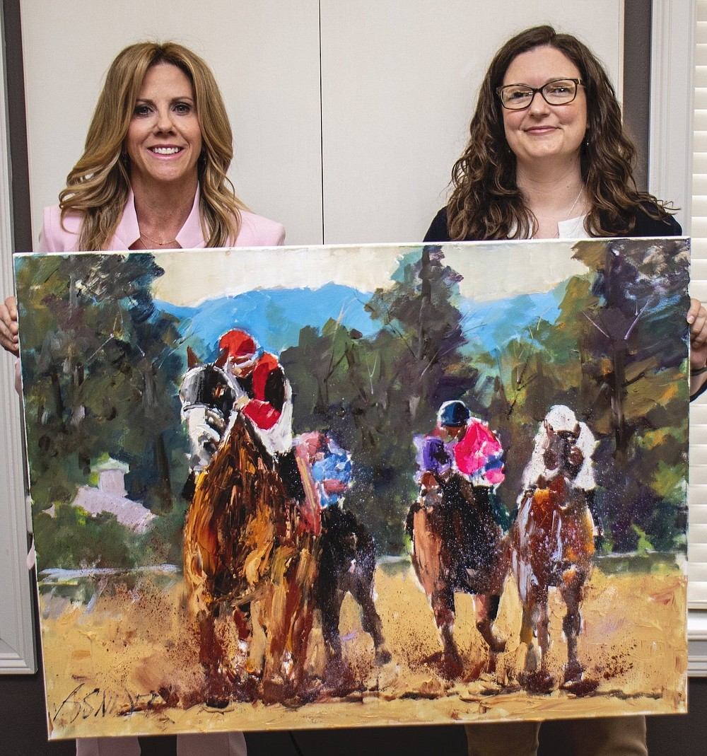 Evolve Gala co-chair Wendy Hannah (left) and auction committee chair Erin Whitt are off to the races with an oil painting by Bob Snider, among the auction items for the Centers for Youth and Families' April 16 virtual gala. (Arkansas Democrat-Gazette/Cary Jenkins)